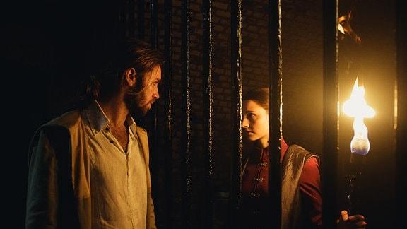 Mick (Gil Ofarim) und Milena (Svenja Jung) blicken von beiden Seiten duch ein massives Gitter.
