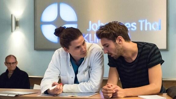 Tom (Tilman Pörzgen, 2.v.l., mit Komparse, l.) versucht herauszufinden, was Alex (Fabian Lichottka, r.) fehlt und findet nach und nach mehr Symptome ...