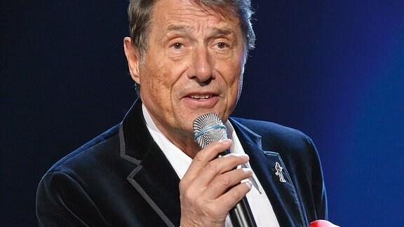 Udo Jürgens - mit dem Mikrofon in der rechten Hand - singend.