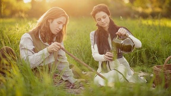 Mick (Gil Ofarim) und Milena (Svenja Jung) beim Picknick auf einer Wiese.