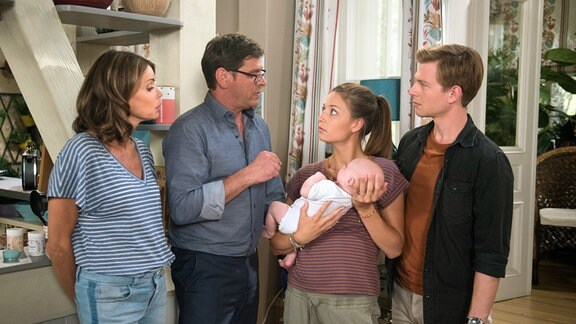 Leonie (Lena Meckel, 2.von rechts) steht mit Cornelius (Tom Mikulla, 2.von links) s Laurenz (Volkmar Leif Gilbert, rechts) und Hilli ( Gerit Kling, links) in einem Wohnraum. Leonie hält ein Baby in den Armen.