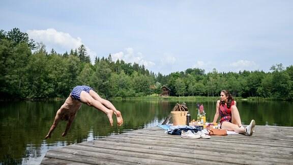 Joshua (Julian Schneider, links) springt in einen See. Denise (Helen Barke, r.) sitzt auf einem Holzsteg.
