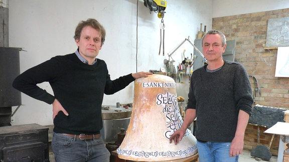 Tobias David Albert, Schriftgestalter und Carsten Theumer, Bildhauer, vor einem kleinen Glockenmodell. Die beiden Künstler sind für die Glockenzier, die Inschriften und Abbildungen auf den sechs neu gegossenen Glocken verantwortlich