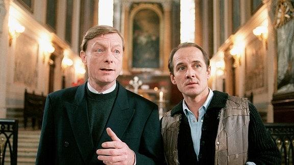 Der Superintendent (Otto Sander,li) und Pfarrer Ohlbaum (Ulrich Mühe) predigen Gewaltlosigkeit bei den Montagsdemonstrationen in der Nikolaikirche.