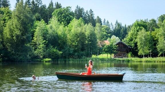 Henry (Patrick Dollmann, links im Wasser) zieht auf einem Waldsee das Boot mit Jessica (Isabell Ege, r.) zurück an Land.