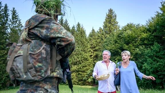 André (Joachim Lätsch, links) und Linda (Julia Grimpe, rechts) erschecken sich fast zu Tode, als vor ihnen ein Soldat (Komparse, ganz links) in Tarnkleidung aus der Deckung springt.