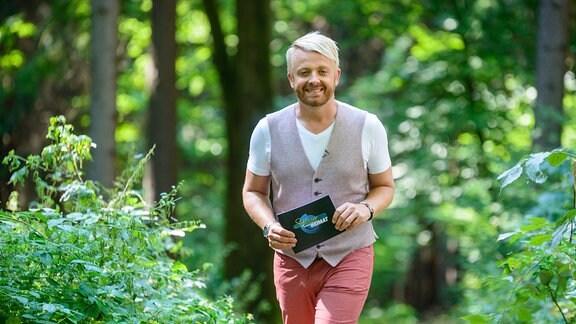 Moderator Ross Antony läuft durch einen Wald.