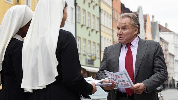 Wöller (Fritz Wepper, r.) überrascht die Novizinnen Lela (Denise M'Baye, l.) und Claudia (Mareike Lindenmeyer, M.) beim Verteilen von Flugblättern gegen die Errichtung eines Truppenübungsplatzes auf dem Klostergelände.
