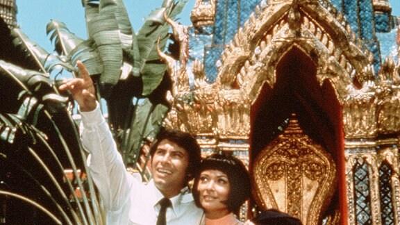 Der frischverliebte Co-Pilot Chris Bergen (Roy Black) lässt sich von Tamazin (Zienia Merton) die Sehenswürdigkeiten von Bangkok zeigen. Sie stehen vor einer farbenprächtigen Pagode.