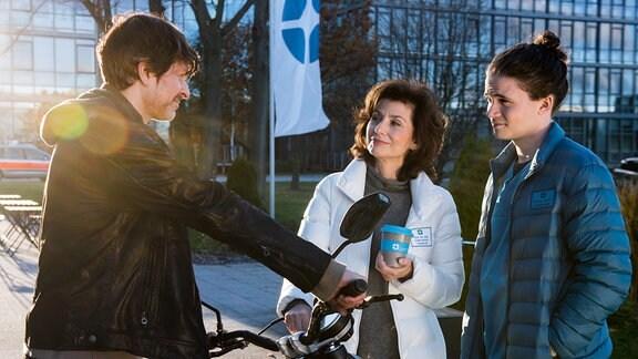 Prof. Karin Patzelt (Marijam Agischewa, links)  steht mit  mit Tilman Pörzgen (rechts) vor Stefan Lochner (Oliver Elias, links), der ein Motorrad in den Händen hält.