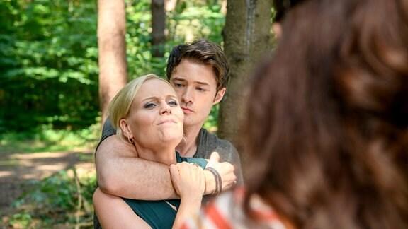 Joshua (Julian Schneider, Mitte) hält mit seinem rechten Arm  Annabelle (Jenny Löffler, links) fest. Denise (Helen Barke, rechts) steht mit dem Rücken zur Kamera.