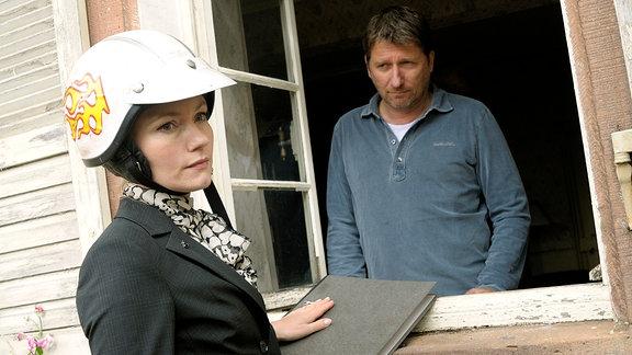 Anwältin Sarah (Johanna Christine Gehlen), mit Motorardhelm,  steht vor einem Fenster. Gegenspieler Peter (Michael Fitz) sieht aus dem Fenster heraus.