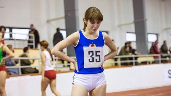 Anna (Judit Bárdos) trauert erkennbar. Sie steht in einer Sporthalle.