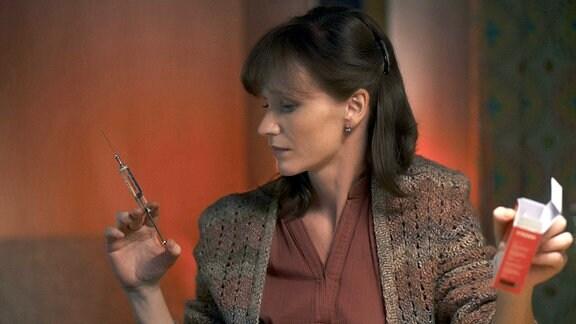 Annas Mutter Irena (Anna Geislerová, r.) hält eine Spritze in der Hand.