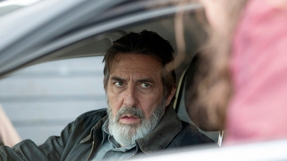 Michael Maguire (Ciarán Hinds)  blickt aius einem Auto.