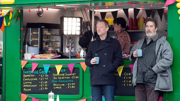 Detective Inspector Jimmy Perez (Douglas Henshall, li.) mit Michael Maguire (Ciarán Hinds) vor einem Verkaufsstand.