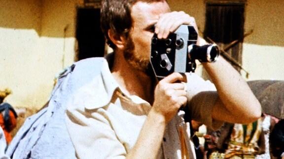 Klaus-Dieter Michel hält eine Schmalfilmkamera vor sein Gesicht