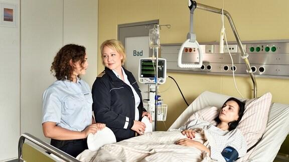 Nele (Floriane Daniel, mitte) und Julia (Wendy Güntensperger, links) stehen neben einem Krankenhausbett, in dem die Segelschülerin Nadine Rückert (Mimi Fiedler, rechts)  liegt.