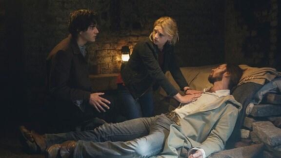Arman (Francois Goeske, l) und Charlie (Sinje Irslinger) stehen hinter einem Schlafenden.