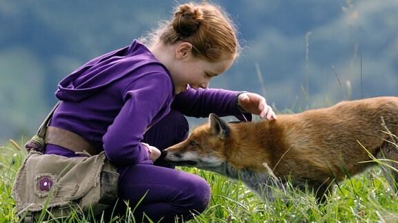 Lila (Bertille Noël-Bruneau) streichelt einen Fuchs.