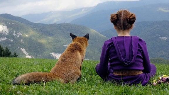 Lila (Bertille Noël-Bruneau) sitzen mit dem Rücken zur Kamera und blicken gemeinsam in die bergige Ferne.