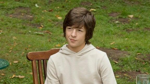 Paul (Julian König) an einem gedeckten Tisch im Freien.