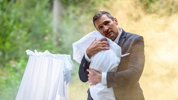 Christoph (Dieter Bach) presst ein Baby an sich