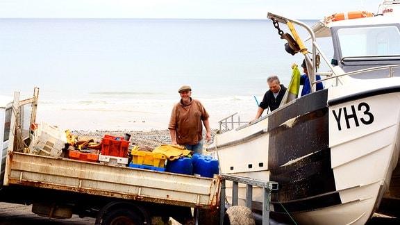 John Davies mit seinem Boot. Ein Kleintrsansporter holt Fisch ab.