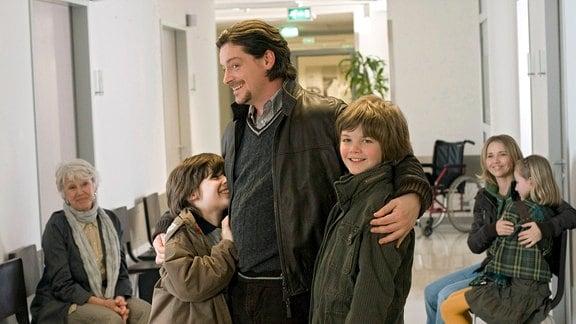 Hannes (Fritz Karl, Mitte) hält  Bruno (Orlando Lenzen, 2.v.li.) und Jonathan (Paul von Kunhardt, 3.v.re.)in seinen Armen. iAstrid (Maria Sebaldt, li.) und Hannes neue Liebe Lilli (Tina Ruland) mit ihrer Tochter Susi ((Johanna Kroll) sind im Hintergrund zu sehen.