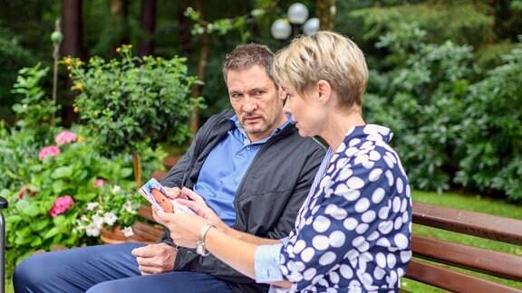 Linda (Julia Grimpe, r.) und Christoph (Dieter Bach, l.)sitzen auf einer Gartenbank und betrachten Bilder.