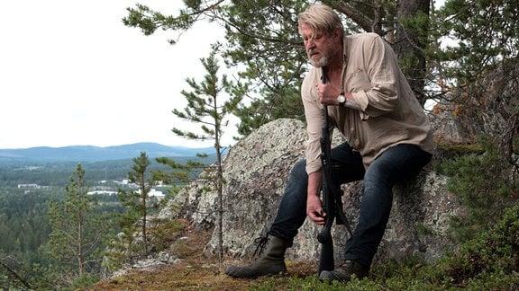 Erik Bäckström (Rolf Lassgård) sitzt in bergiger Umgebung auf einem  großen Stein. Er hält sich eine Waffe an das Kinn.