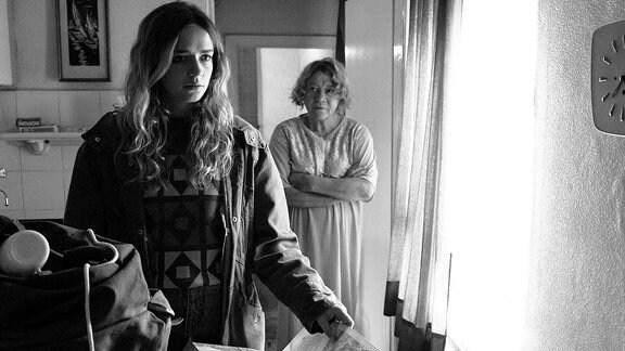 Mutter (Veronika Nowag-Jones, r.) und Tochter (Sarina Radomski) stehen in einem Wohnraum.