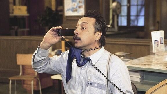 Szene mit Wolfgang Stumph als Wolfgang Stankoweit - er hält einenen  Telefonhörer ans Ohr; den Apparat in der linken Hand.
