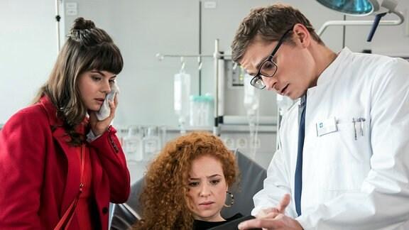Elias Bähr (Stefan Ruppe, r.) zeigt  Ramona Hinze (Sandra Julia Reils, l.) und Kim Kallies (Sarah Hannemann, M.),Untersuchungsergebnisse..