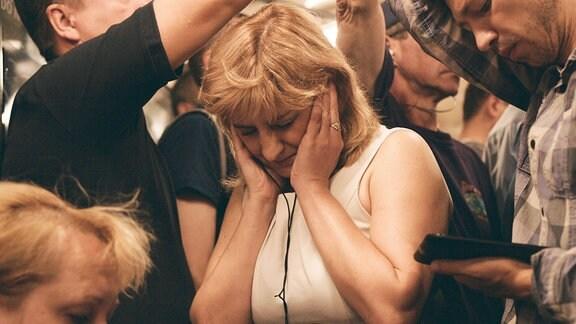Die 50-jährige Oksana  stützt den Kopf auf ihre Hände.