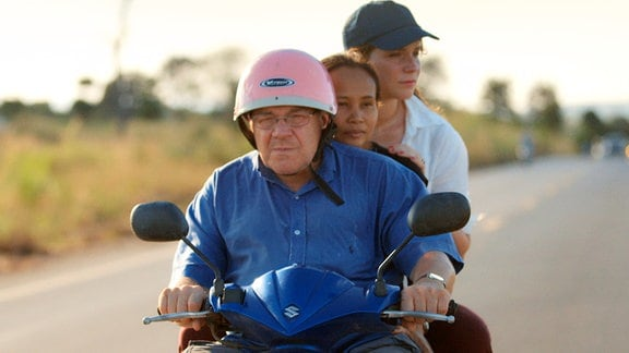 Die drei Protagonisten Dieter, seine Tochter, die Regisseurin Carolin und seine Verlobte Tukta auf dem Roller in Thailand.