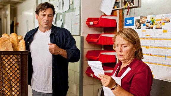 Oliver Maibach (Thomas Sarbacher) und seine Mutter Elisabeth (Petra Kelling)stehen in einer Bäckerei. Die Mutter hält ein Papier in der linken Hand und starrt darauf.