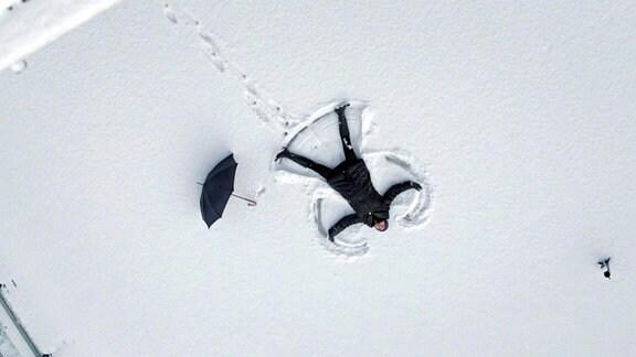 Ines Rastig liegt mit usgebreiteten Amwn auf dem Rücken im Schnee.