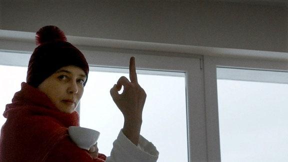 Ines Rastig hält die Hand nach aben und streckt den Mittelfinger nach oben. Sie Blickt in die Kamera und trägt eine Pudelmütze.