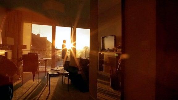 Ines Rastig steht am großflächigen Fenster eines Wohnraumes. Diue Sonne scheint herein und erzeugt am Fenster einen Lichteffekt..