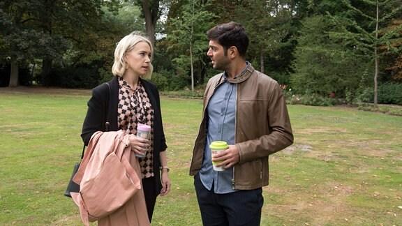 Cem (Varol Sahin, r.) und Amelie (Lara-Isabelle Rentinck, l.) stehen in einer Parklandschaft.