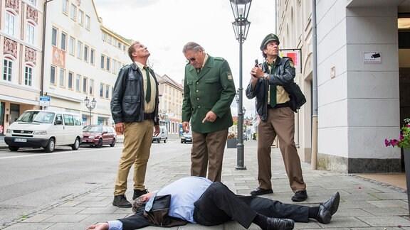 Girwidz (Michael Brandner, M.), Hubert (christian Tramitz, l.) und Staller (Helmfried von Lüttichau, r.) stehen auf einer Stadtstraße. Vor ihnen ligt der Bürgermeister (Komparse).