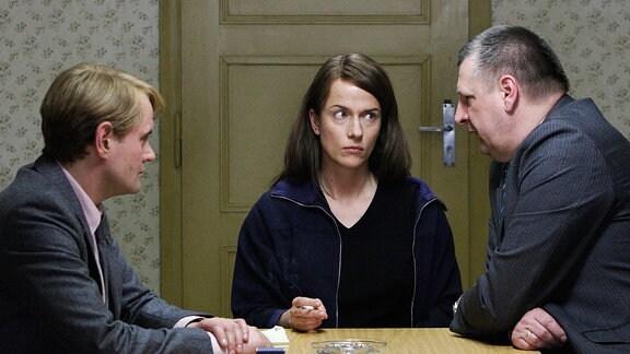 Jan (Devid Striesow), Bettina (Claudia Michelsen) und Referatsleiter MfS (Roland May)  sitzen an einem Tisch (von links).