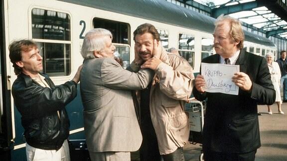 Thanner (Eberhard Feik, r.) und Schimanski (Götz George, 3.v.l.) stehen mit  Grawe ( Andreas Schmidt-Schaller, l.) und Fuchs (Peter Borgelt, 2.v.l.)auf einem Bahnsteig des Bahnhofs Duisburg (Bahnhofshalle).Im Hintergrund ein  Schnellzugwagen. Über dem Wagen ist ein Stück der typischen Bahnsteighalle  des Duisburger Hauptbahnhofes  zu erkennen.