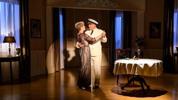 André (Joachim Lätsch, rechts)  und Linda (Julia Grimpe, l.) tanzen in einem wenig beleuchteten Raum. André trägt eine weiße Uniform.