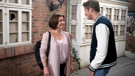 Alex (Philipp Oliver Baumgarten, r.) und Astrid (Claudia Schmutzler, l.) im gemeinsamen Gespräch vor einem Wohnhaus.