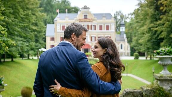 """Denise (Helen Barke, r.) und Christoph (Dieter Bach, l.) haben jeweils mit einem Arm den Anderen umschlungen; sie stehen vom """"Fürstenhof""""."""