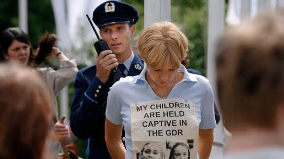 Sara Bender (Veronica Ferres) stteht an einem Mast, gefesselt.  Hinter ihr ein Polizist mit Sprechfunkgerät. An Saras Brust hängt ein   Transparent.
