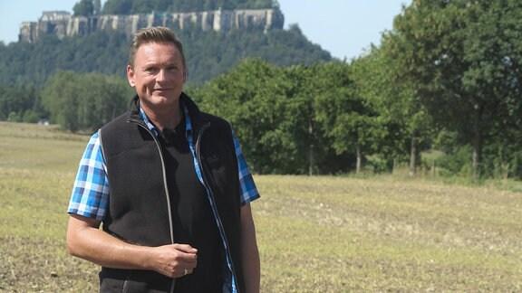 Moderator Axel Bulthaupt - vor einem Wald stehend, dahinter ein großer Schrammstein.,