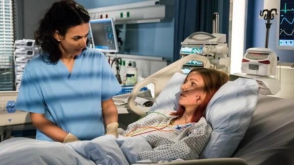 Dr. Sherbaz (Sanam Afrashteh, l.) untersucht Elena Kleinert (Katrin Heß, r.), die in einem Krankenhausbett liegt.